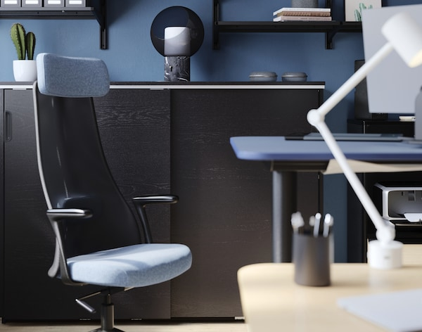 Office swivel chair in blue/black in front of a GALANT storage unit with sliding doors.