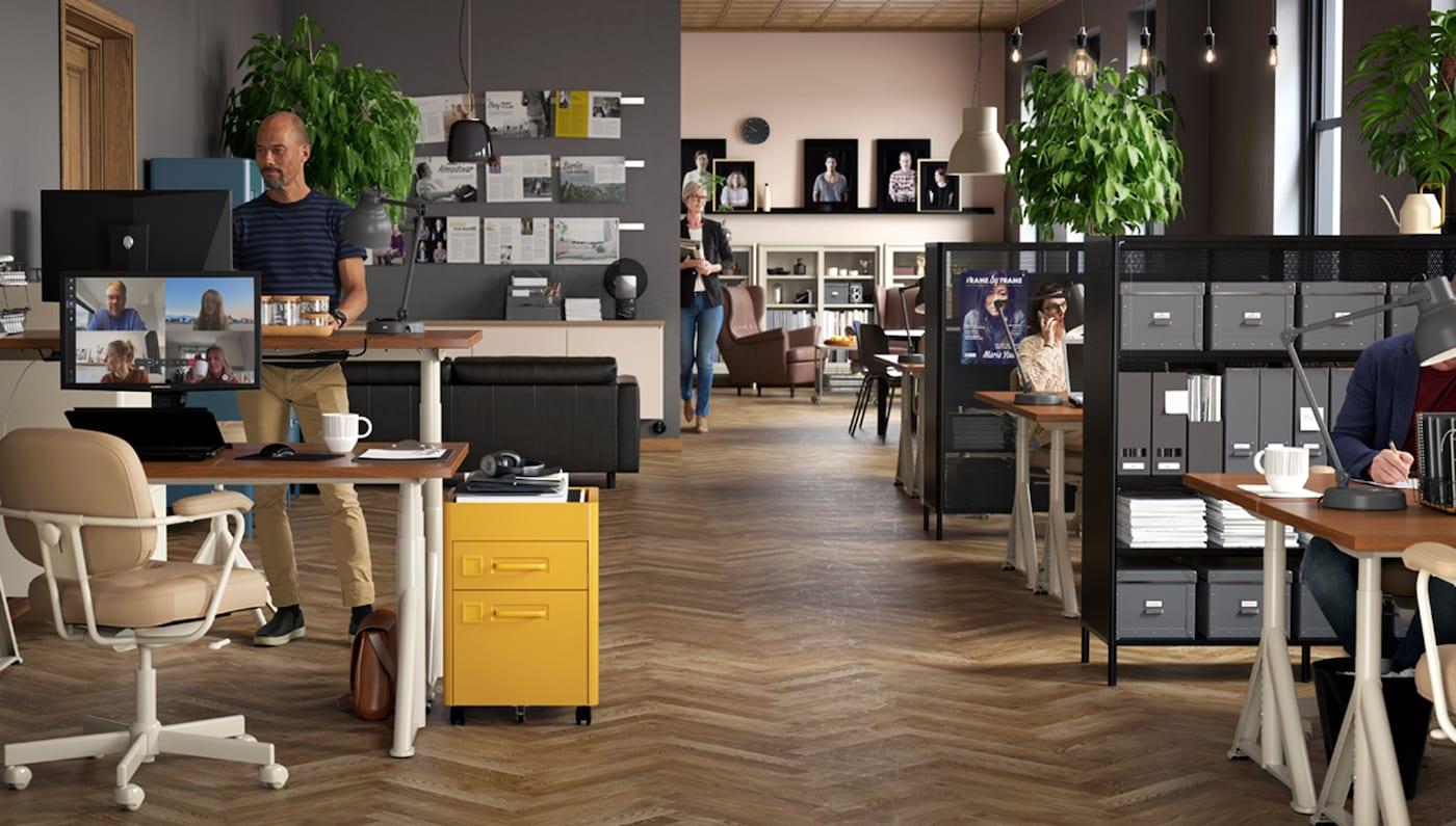 Oficina con escritorios para trabajar de pie/sentado IDÅSEN en beige, sillas giratorias, varias cajoneras de oficina y algunas personas trabajando.