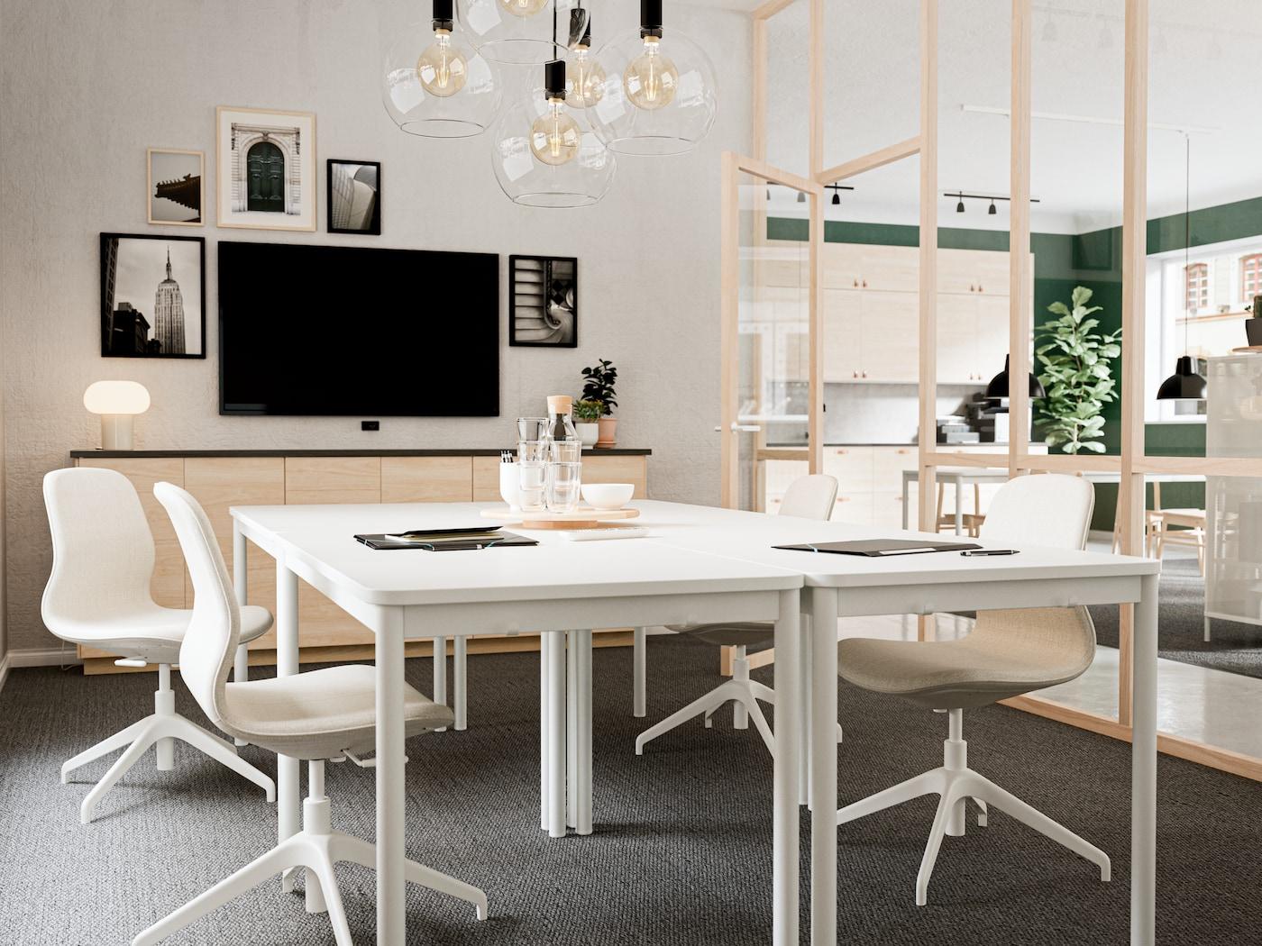 Oficina de trabajo con auténtica mesa blanca de IKEA modelo TOMMARYD, con sillas blancas que complementan el espacio de trabajo. Una pantalla para proyectar, utensilios de oficina y luces para iluminar la sala.
