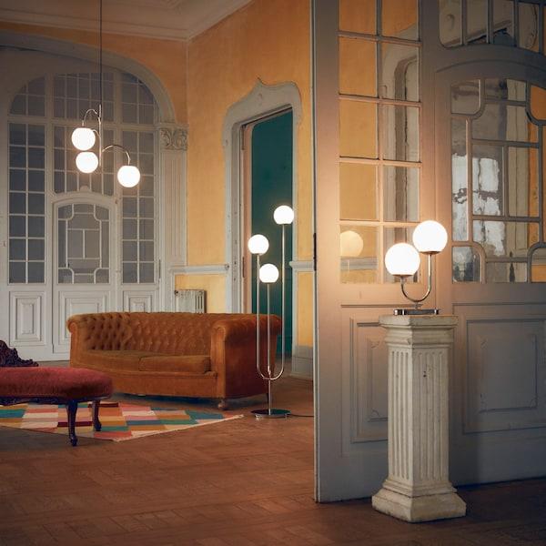 Ogromny pokój, w którym wyeksponowano trzy zapalone lampy SIMRISHAMN ze szklanymi kloszami – lampę wiszącą, podłogową i stołową.