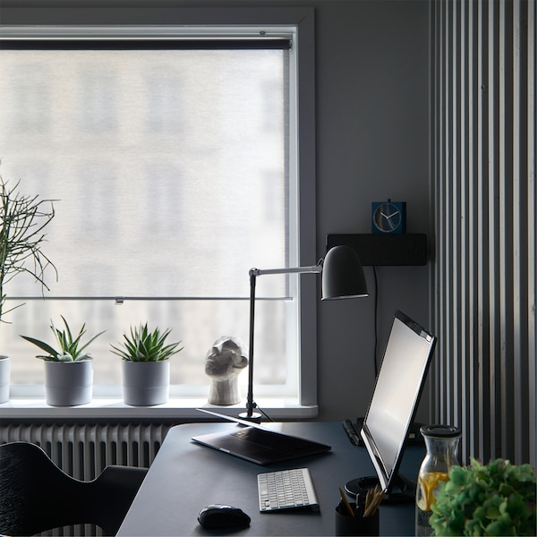 Okna w domowym biurze z zaciągniętą niemal do  samego dołu szarą roletą SKOGSKLÖVER, za biurkiem z lampą i monitorem komputera.