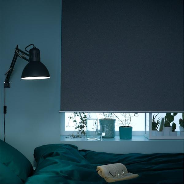 Okno w sypialni, prawie całkowicie zasłonięte szarą roletą zaciemniającą.