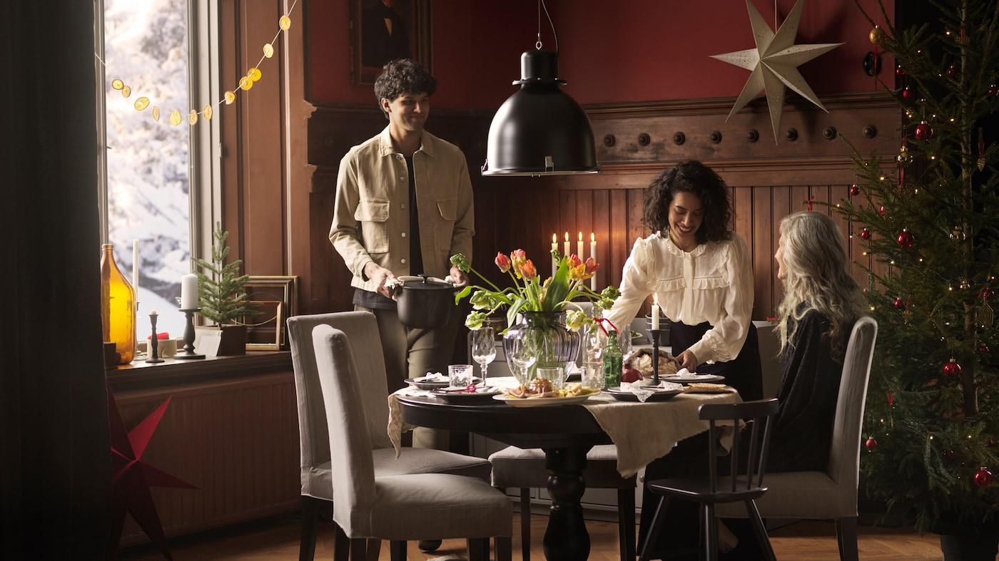 Oko okruglog INGATORP stola ukrašenog svežim cvećem okupilo se troje ljudi kako bi zajedno jeli za praznike.
