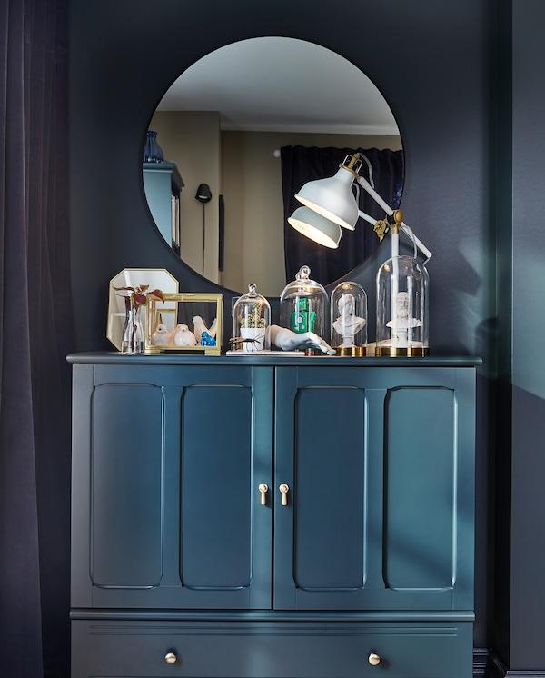 Okrągłe lustro, granatowo-zielona szafka i drobne elementy dekoracyjne stojące wewnątrz szklanych kopuł i witryn.