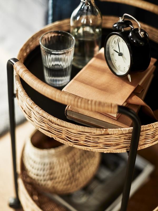 Okrugla LUBBAN kolica na dva nivoa, od ratana i metala, s knjigama, vodom i satom na vrhu, i raznim predmetima ispod.