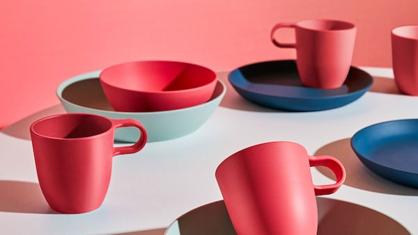 Okrúhly stôl s červenými, tmavomodrými a svetlozelenými taniermi, miskami a hrnčekmi zo série IKEA TALRIK z PLA plastu.