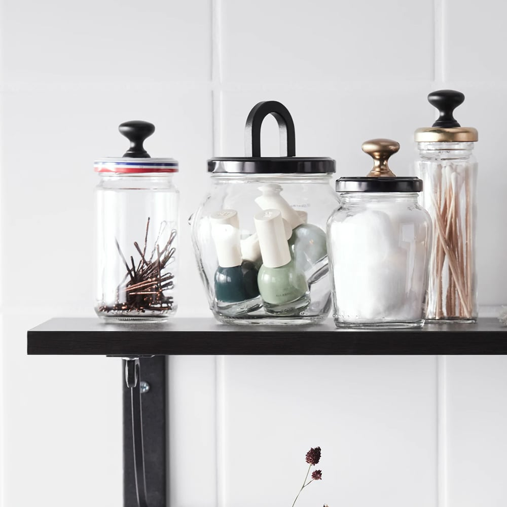 Old jars on a wall shelf that have been reused to store hair pins, nail polish bottles and cotton balls