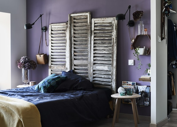 Old shutters used as a headboard above a bed.