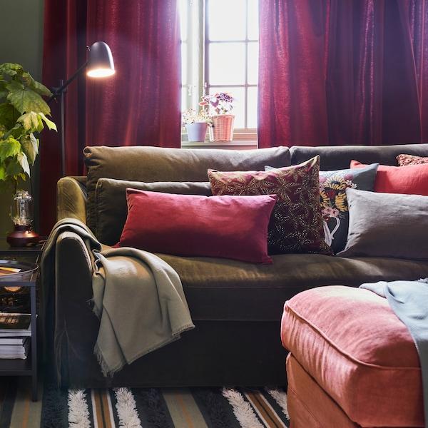 Oliwkowozielona sofa z mnóstwem poduszek w różnych kolorach, pasiasty dywan, jasnoczerwony podnóżek i czarna lampa podłogowa.