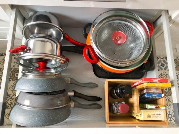 Ollas y sartenes ordenadas en el cajón del a cocina