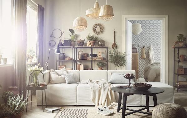 Olohuone, jonka sisustuselementteinä ovat rottinkikalusteet, puu ja beige sohva.
