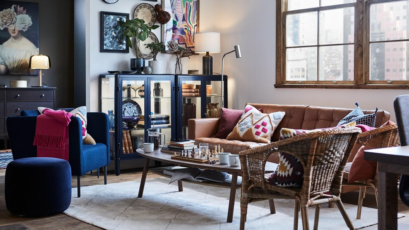 Olohuone, jossa on nojatuolit ja sohva sohvapöydän ympärillä, sohvan vasemmalla puolella esittelykaappi.