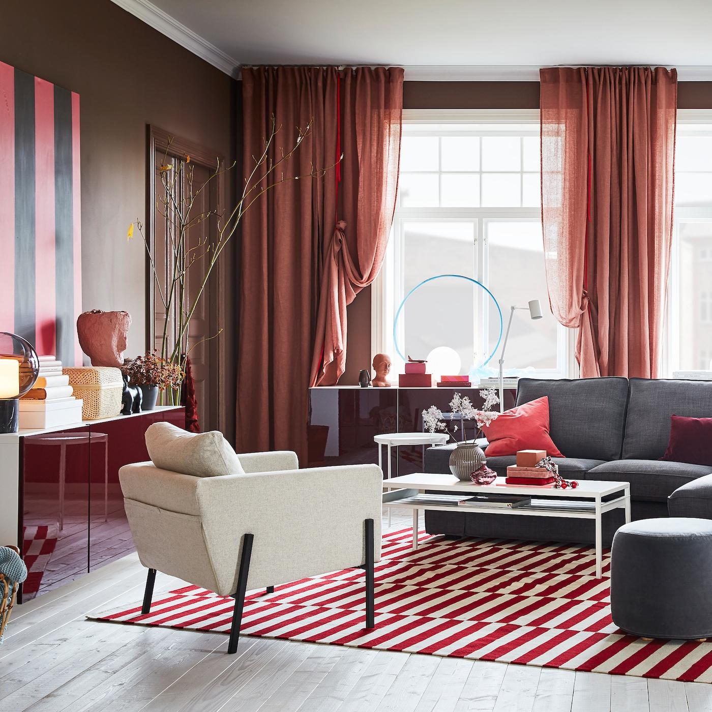 Olohuone, jossa rusehtavan roosat verhot, puna-valkokuvioitu matto, harmaa sohva sekä seinään kiinnitetyt kaapit, joissa korkeakiiltoiset, punaiset ovet.