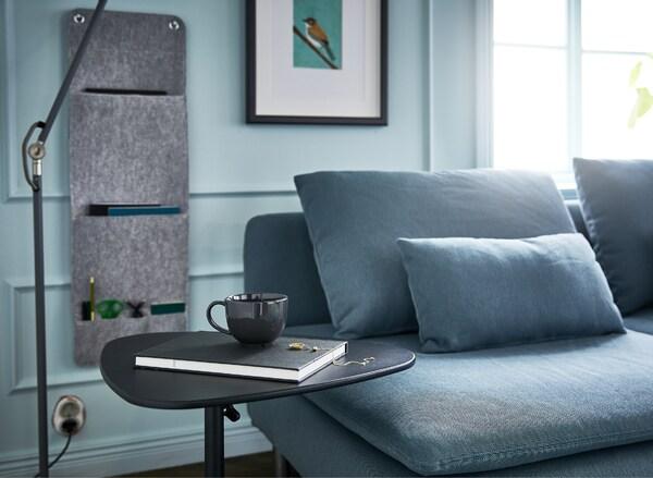Olohuone, jossa sohva, lattiavalaisin, seinäsäilytystä sekä säädettävä taso kannettavalle tietokoneelle.