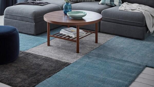 Olohuoneen lattialla vierekkäin monta eriväristä STOENSE-mattoa. Mattojen päällä sohvapöytä ja sohva.