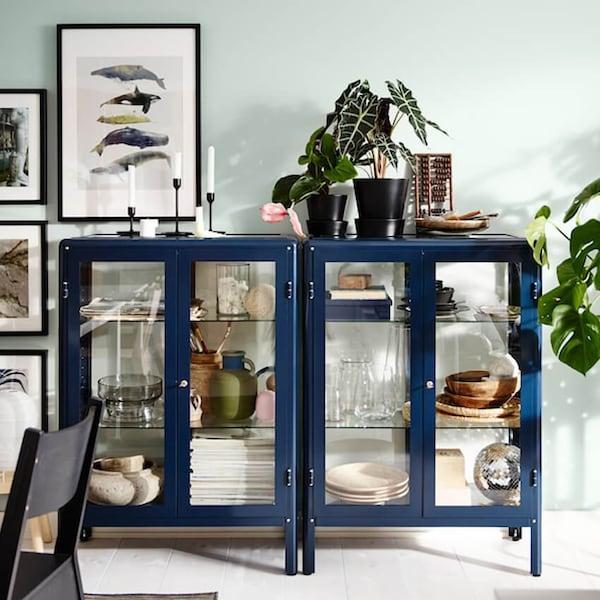 Olohuoneen säilytystä sinisessä FABRIKÖR-vitriinikaapissa jossa lasiovet.