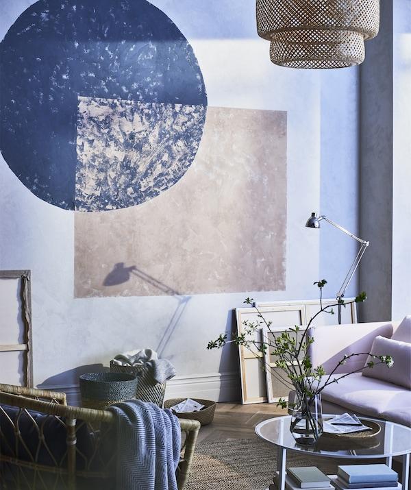 Olohuoneen seinään on maalattu geometrisia muotoja. Kuvassa myös vaaleanpunainen sohva ja korituoli.