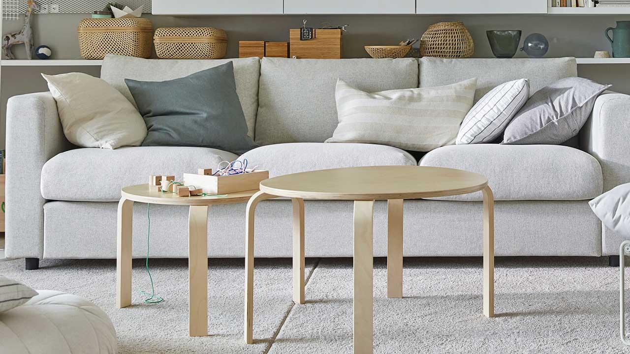 Olohuoneen vaalea sohva, edessä kaksi puista pyöreää sohvapöytää