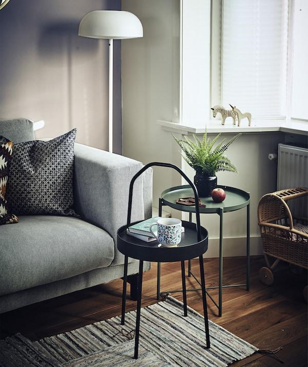 Olohuoneessa on kaksi pientä pyöreää sivupöytää sohvan vieressä.