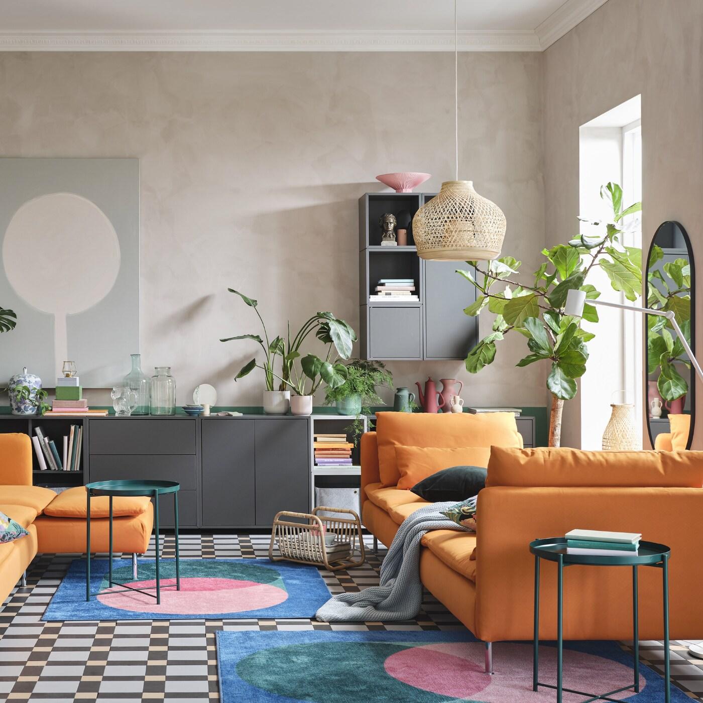 Olohuoneessa on oranssi divaanisohva ja oranssi divaani, harmaa säilytyskaluste, värikkäitä mattoja sekä kaksi vihreää tarjotinpöytää.