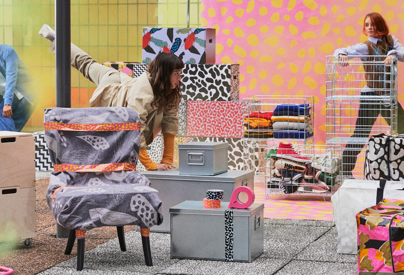 OMBYTE boxes made from cardboard with wild patterns, metal and wire. A grey blanket is wrapped and taped around a chair.