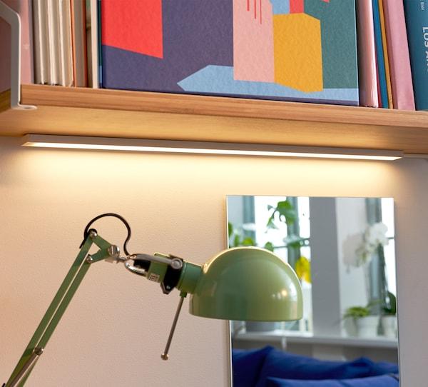 OMLOPP إضاءة سطح عمل LED لون أخضر، مع مرآة خلفها تعكس صورة الغرفة وفوقها رف مملوء بالأغراض الملونة.