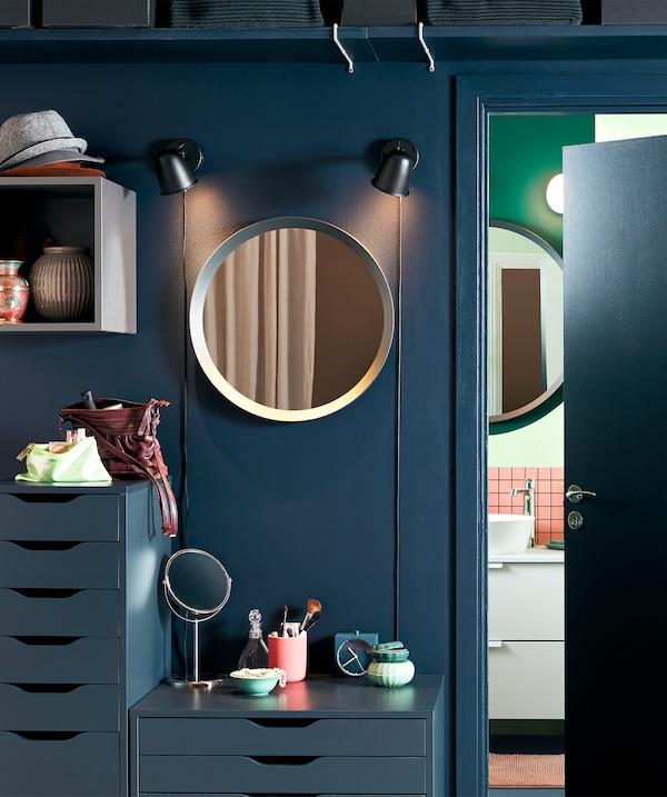 Område uden for et badeværelse, indrettet som et enkelt sminkebord med spejle, kommoder og makeup.