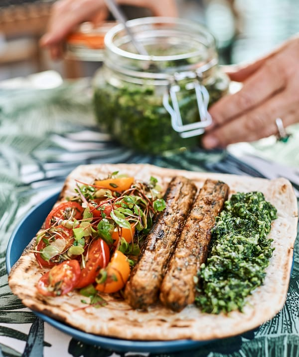 On a blue plate, flatbread with pesto, sausages and tomato salad, hands close a glass jar of pesto.
