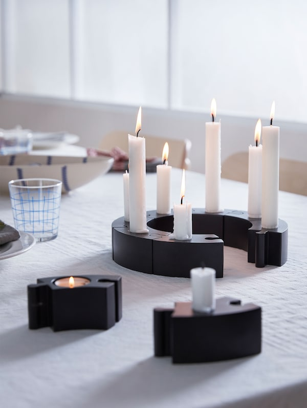 On a dining table, candles are lit and placed on black VÄRMER puzzle candlesticks.