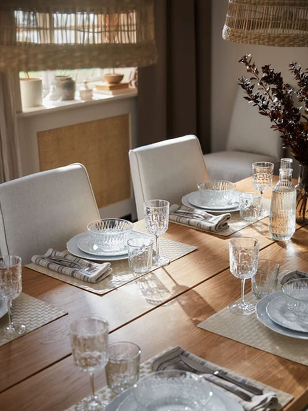 On a table are place settings with placemats, plates, glass bowls, glasses, wine glasses, cutlery and linen napkins.