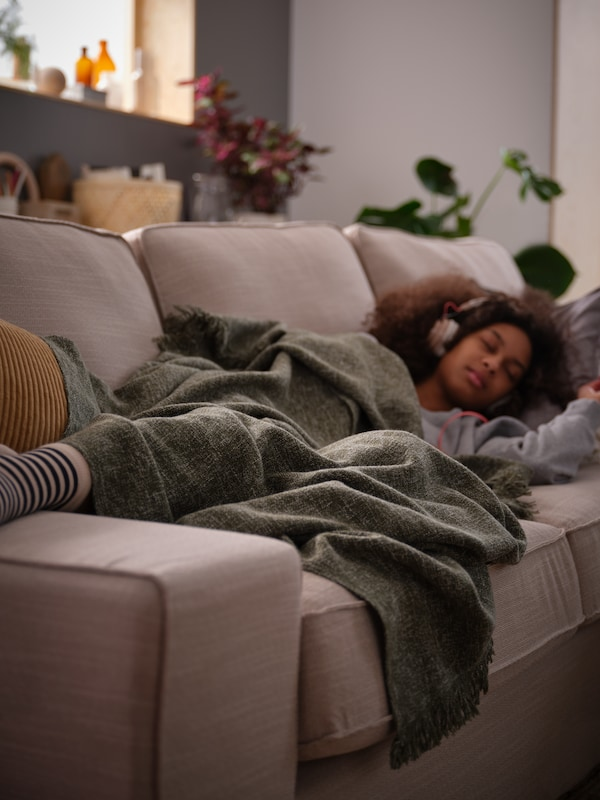 On an autumn afternoon, a preteen girl wearing headphones takes a nap on a KIVIK sofa with an INGRUN throw draped over her.
