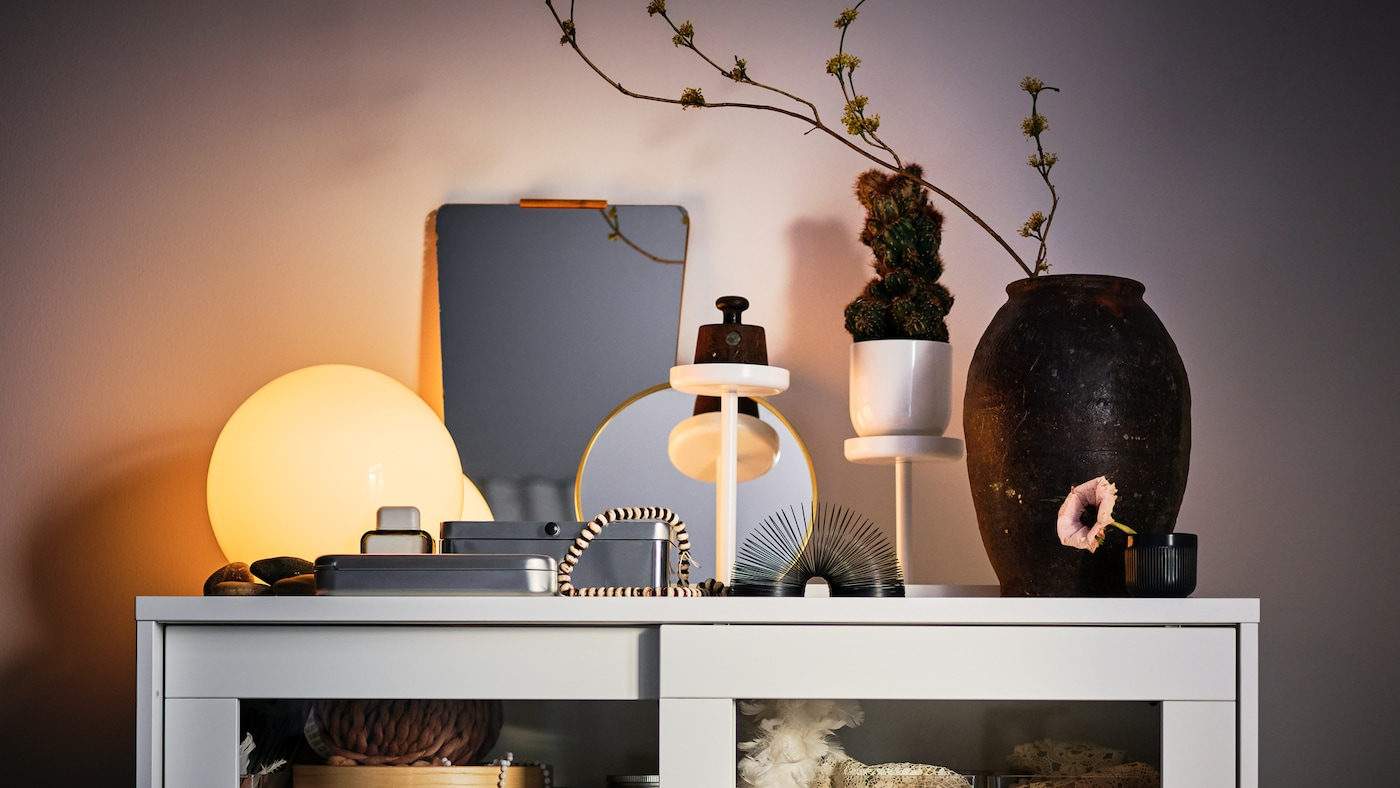 On top of a white SYVDE glass-door cabinet stands a lit, white FADO table lamp amid multiple decorative items.