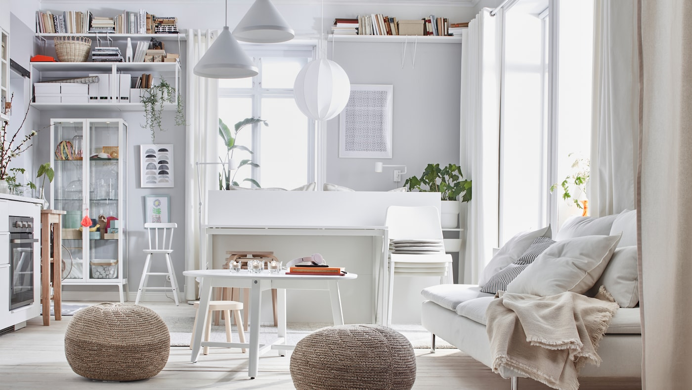 One-room apartment interior with a light color scheme: bed, sofa, kitchenette, storage, and two SANDARED pouffes.