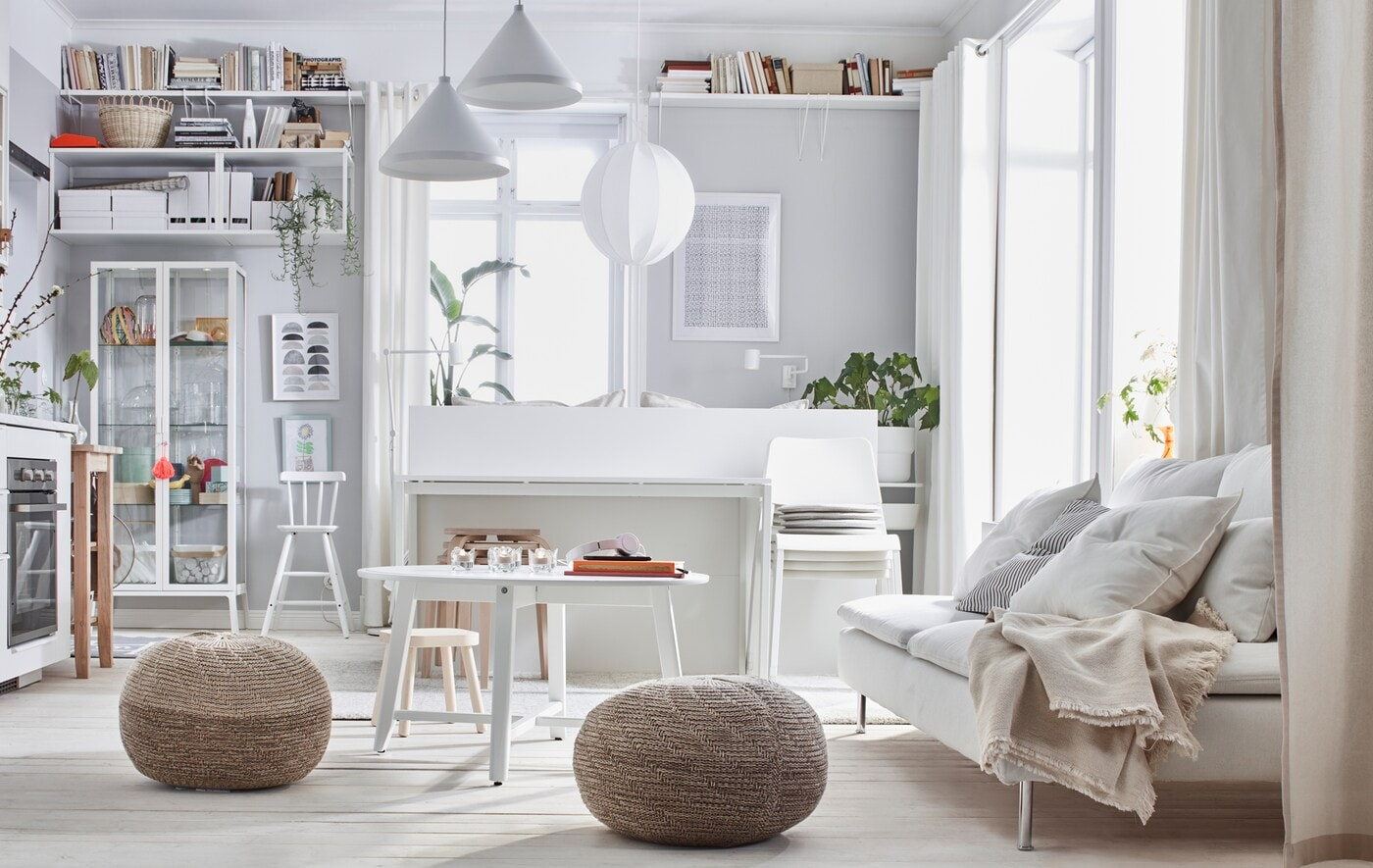 One-room apartment interior with a light colour scheme: bed, sofa, kitchenette, storage, and two SANDARED pouffes.