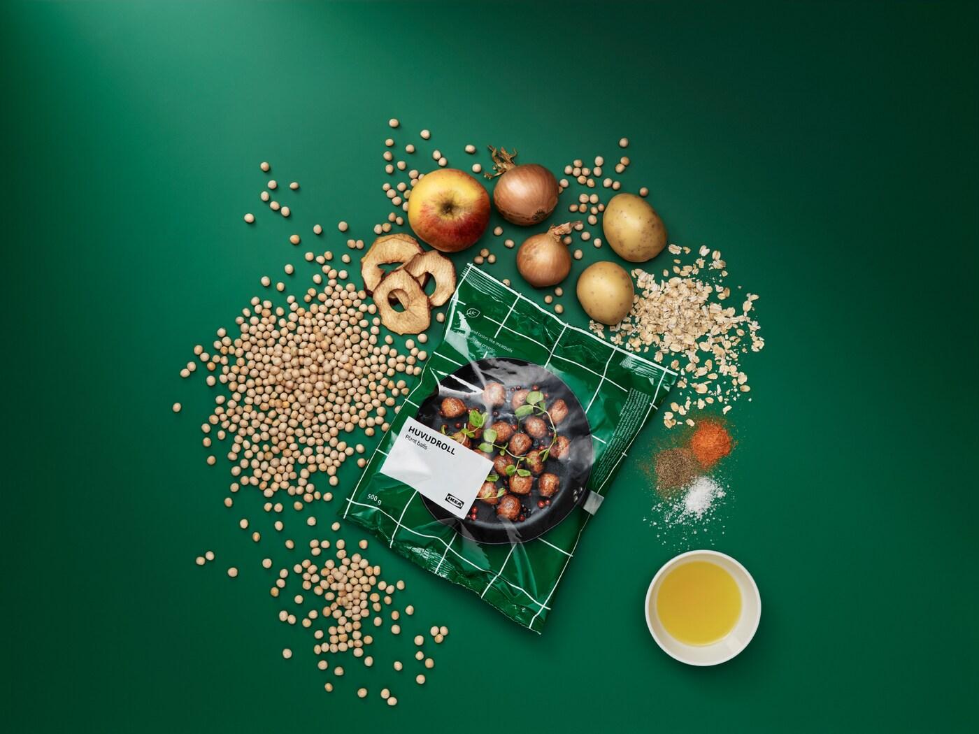 Opakowanie klopsików roślinnych HUVUDROLL otoczone przez surowe składniki: groch, owies, ziemniaki, cebule, jabłka i przyprawy.
