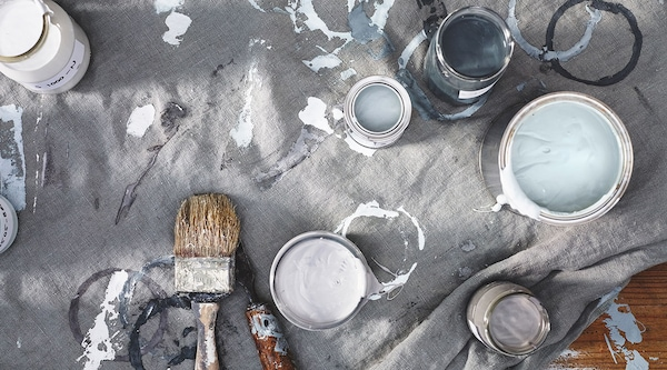 Open cans of paint and paint brushes on a floor