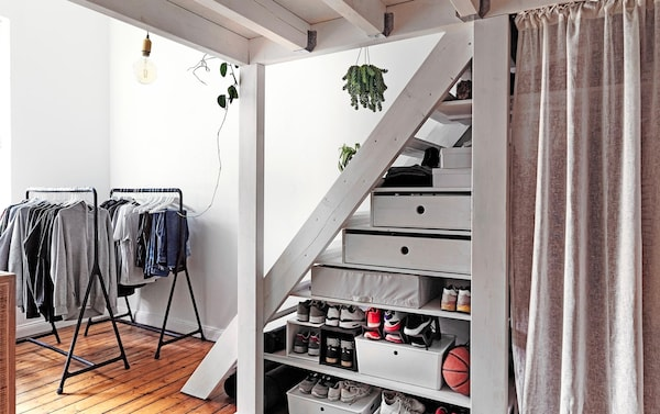Open clothes rails and storage boxes under a flight of stairs