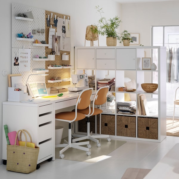 Open concept living space with a long white desk set up for two people.