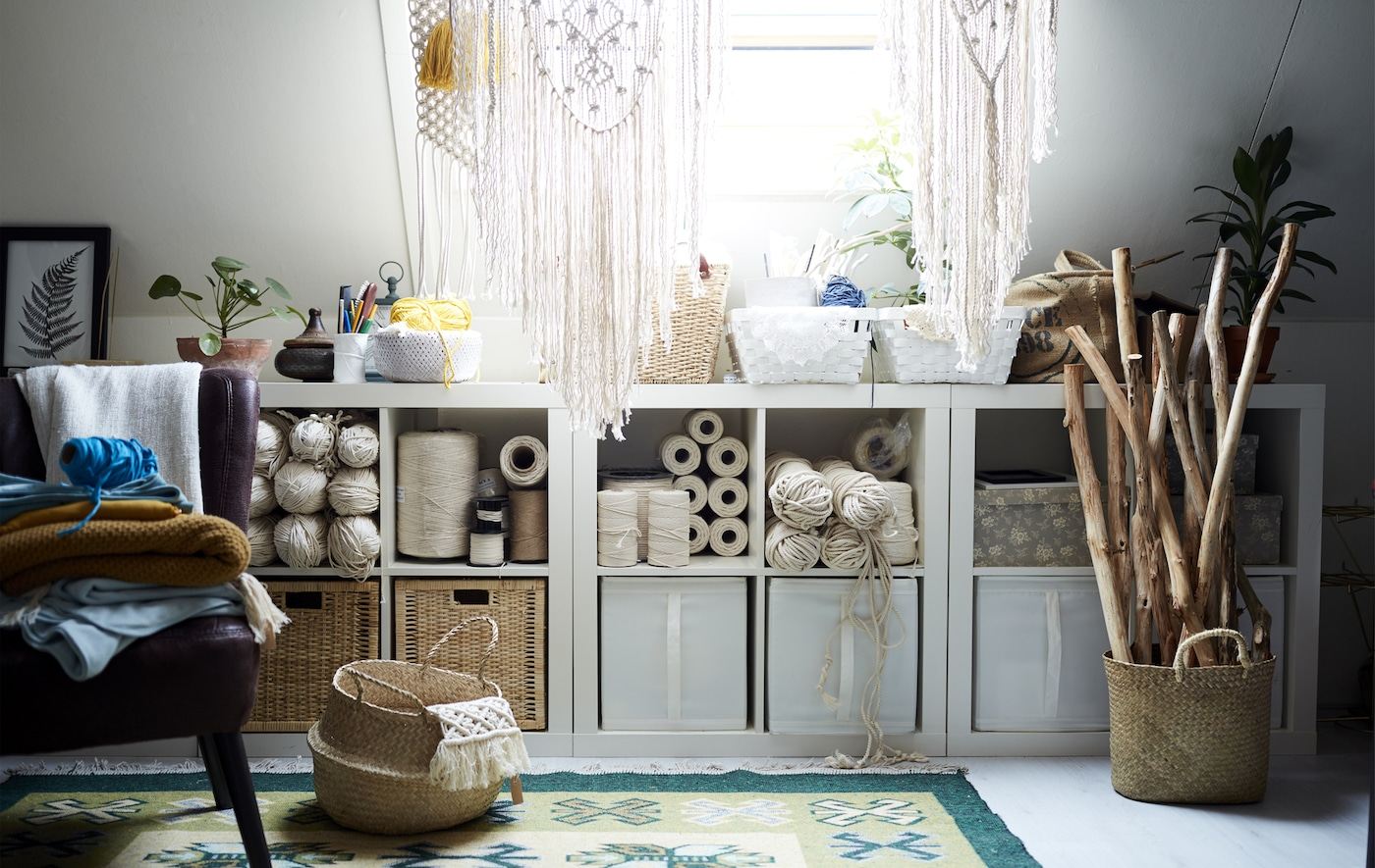 Open storage filled with boxes and creative hobby items, including threads, wooden sticks and hanging macramé items.