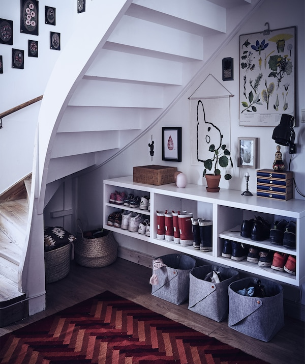 Open under-stairs area with storage baskets and shelves for boots and shoes.