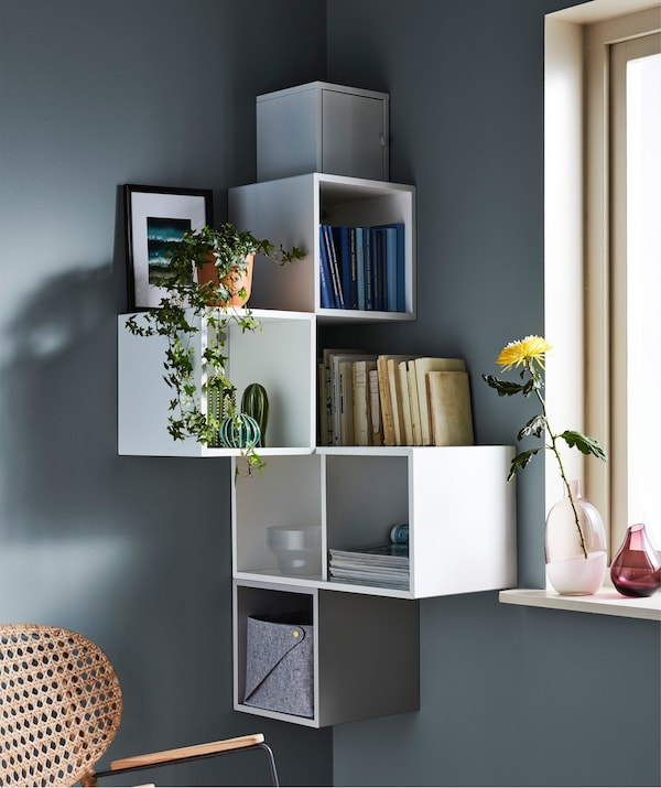 Open wall storage units, in a corner of a grey room, decorated with books, plants and picture frames.