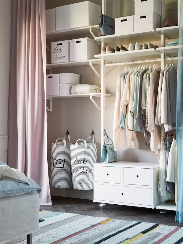 Open wardrobe with curtain. Neatly organized with storage boxes.