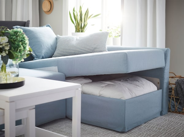 Opened IKEA HOLMSUND corner sofa-bed, in Orrsta light blue, with storage space under the chaise longue for bedding.