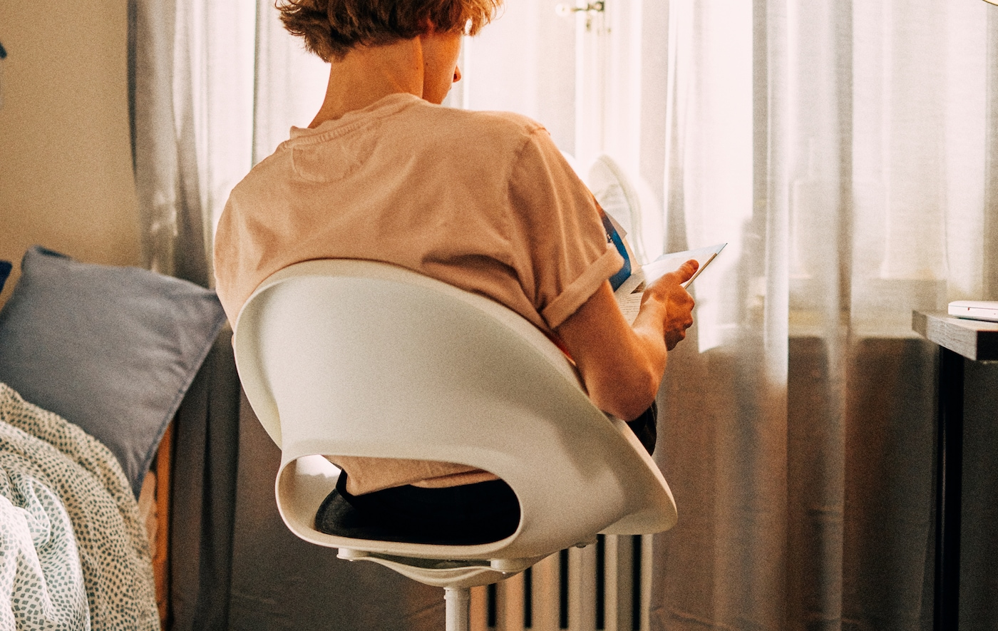 Opiskelija lukee istuen työtuolissa kohti ikkunaa ja lepuuttaa jalkojaan patterin päällä.