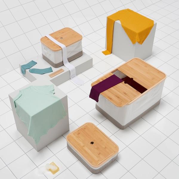 Opstelling van IKEA RABBLA textieldozen in drie verschillende formaten met deksel uit bamboe, op een witte tegelvloer.
