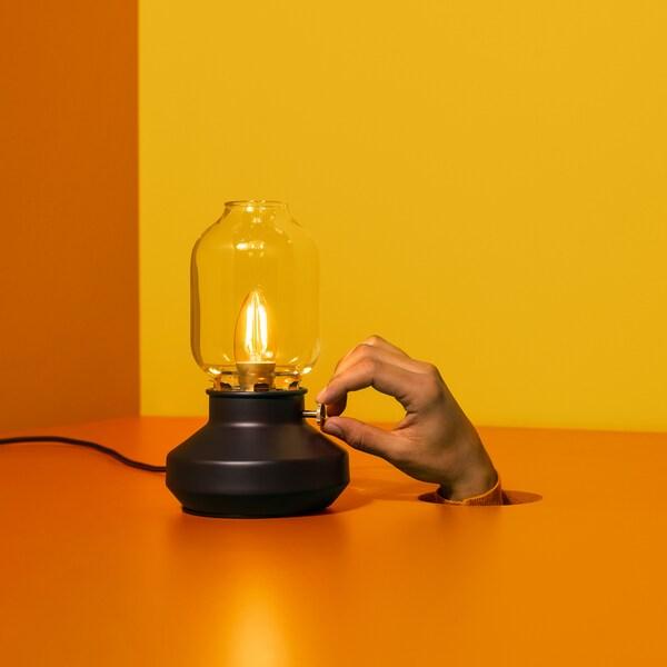 Oranssilla taustalla vanhanaikaisen näköinen pöytävalaisin. Käsi tulee läpi lattiasta ja säätää valaisinta.