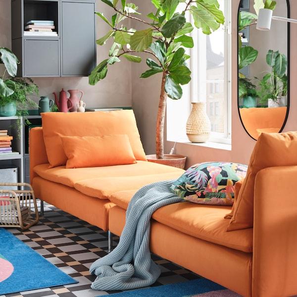 オレンジの寝椅子2台を並べて広いデイベッドをつくっています。上にはブルーのひざ掛けとフローラル模様のクッション。