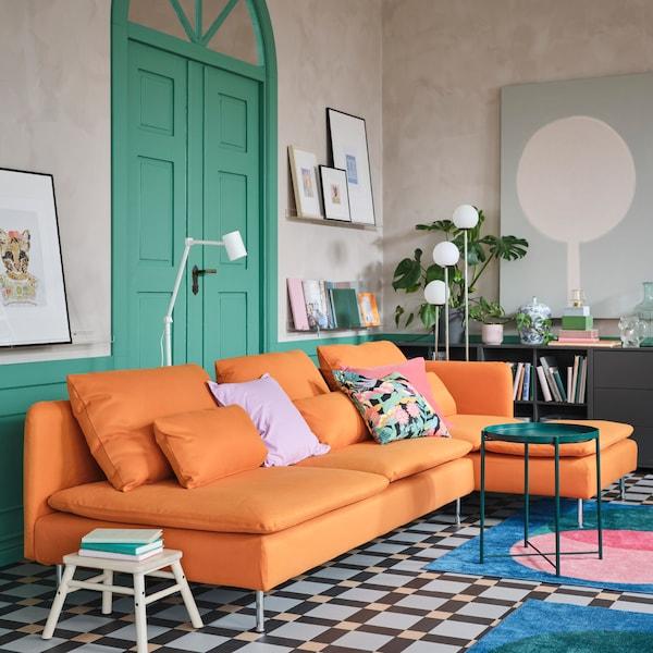 オレンジの4人掛けソファ 寝椅子付き、グリーンのトレイテーブル、ピンク/グリーン/ブルーのラグ2枚、ホワイトのフロアランプ2台。