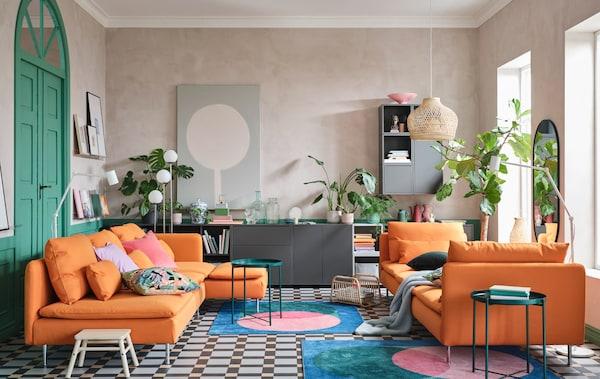 オレンジのソファと寝椅子、グレーのキャビネットコンビネーション、カラフルなラグ、グリーンのトレイテーブルのあるリビングルーム。
