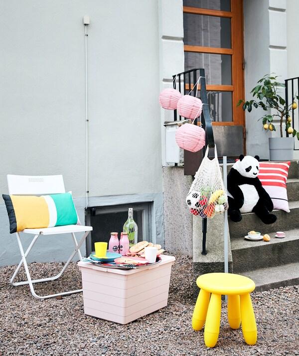 Organisation pour pique-niquer et jouer à l'extérieur d'un bâtiment, avec sièges, petite table, nourriture et boisson, jouets et décorations.